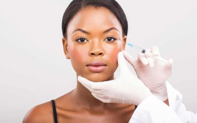 A woman is getting injected with a facial filler by a medspa technician.